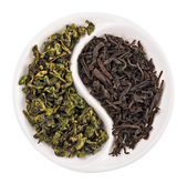 Green leaf tea versus black one in Yin Yang shaped plate, isolat — Stock Photo