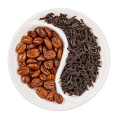 Black leaf tea versus coffee beans in Yin Yang shaped plate, iso — Stock Photo