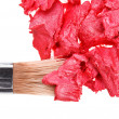 Red lipstick stroke (sample) with makeup brush, isolated on whit - Stock Photo