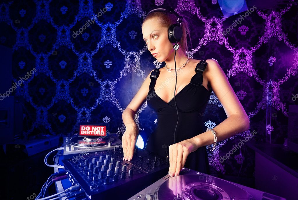 Sexy young blonde lady DJ playing music in night club  Stock Photo #5851698