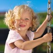 Cute little girl with blond curly hair playing on wooden chain s — ストック写真