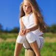 Cute little girl with blond long hair outdoor portrait in front — Stock Photo #5891396
