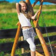 Cute little girl with blond long hair playing on wooden chain sw — Stock Photo #5891404