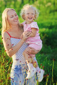 Beautiful mother with infant curly-headed blond daughter on mead — Stock Photo
