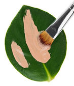 Beige liquid foundation makeup stroke with brush over green leaf — Stock Photo