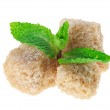 Постер, плакат: Three brown lump cane sugar cubes with peppermint leaves isolat