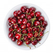 Many red wet cherry fruits (berries) in round plate, isolated on — Stock Photo