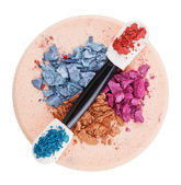 Heap of broken multicolor eyeshadow over makeup sponge, isolated — Stock Photo