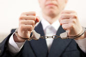 Handcuffs on hands — Stock Photo