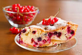 Piece of berry pie on saucer and red currants in bowl — Stock Photo