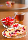 Piece of berry pie on saucer and red currants — Stock Photo