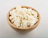 Fresh cottage cheese in wooden bowl — Stock Photo