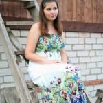 chica joven se sienta en una escalera de madera — Foto de Stock