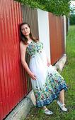 Girl in light dress against metal fence — Stock Photo