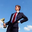 Young businessman with a golden cup — Stock Photo