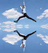 Jumping young businessman in a blue shirt — Stockfoto
