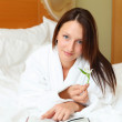 Young woman in bed reading a book — Stock Photo
