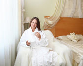 Young woman in white robe drinking tea — Stock Photo