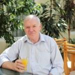 Portrait of old man with orange juice — Stock Photo #5731390