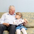 Grandfather and granddaughter reading book — Stock Photo