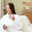 Stock Photo: Young womin white robe drinking tea