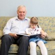 Grandfather and granddaughter reading book — Stock Photo #5773658
