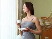 Jovem mulher bebendo chá perto da janela — Foto Stock