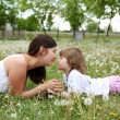 Itlle girl with her mother outdoors - Stock Photo