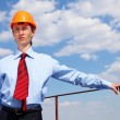 Young engineer in a blue shirt and yellow helmet — Stock Photo