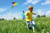 Vader en zoon in de zomer met kite — Stockfoto