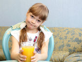 Portrait of little girl with orange juice — Stock Photo