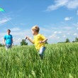 Father with son in summer with kite - Stock Photo