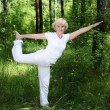 Stock Photo: An elderly woman practices yoga