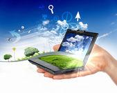 Menselijke hand met laptop en natuur landschap — Stockfoto