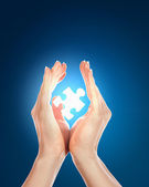 Human hand with a piece of puzzle — Stock Photo