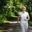 Elderly woman likes to run in the park - Stock Photo