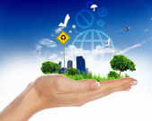 Human hand holding a green city — Stock Photo