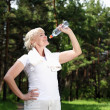 Elderly woman after exercising in the forest — Stock Photo