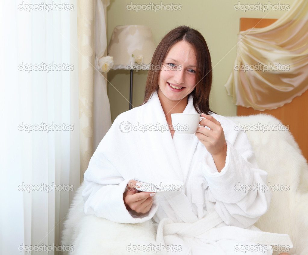 Portrait of young woman in white bath robe holding a cup of tea — Stock Photo #6035653