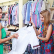 Girl seller helps shoppers — Stock Photo #6124427