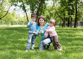 Portrait of mother and children in the park — Stock Photo