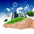 Human hand holding a green city - Stock Photo