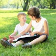 Children in the park reading a book — Stock Photo #6193780