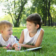 Children in the park reading a book — Stock Photo #6193834