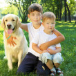 Two brothers in the park with a dog — Stock Photo #6194138