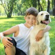 Stock Photo: Tennager boy in the park with a dog