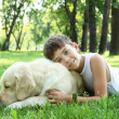Little boy in the park with a dog — Stockfoto