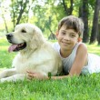 Little boy in the park with a dog — Stock Photo