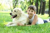 Kleine jongen in het park met een hond — Stockfoto