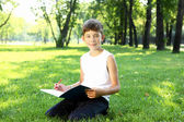 Portrait of a boy with a book in the park — 图库照片